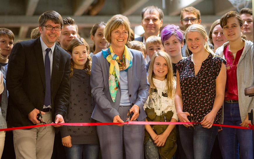 Schulleiter Moser-Kollenda, Bürgermeisterin Nieber und Schulsprecherin Luca Woltemade durchschneiden das Band zur Eröffnung des Selbstlernzentrums.